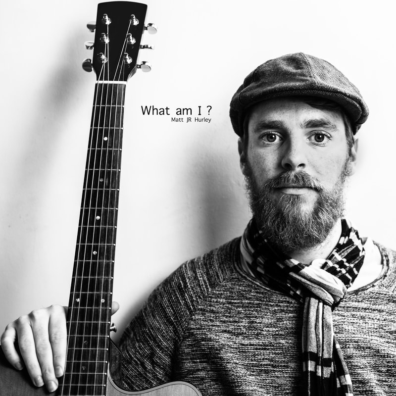 Album cover of bearded musician looking at camera and holding guitar in black and white