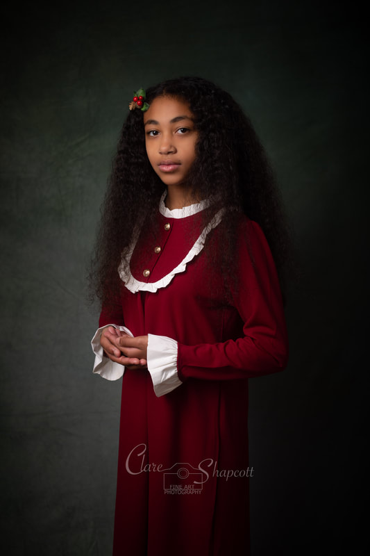 Long, curly haired girl in long red christmas gown has her hands together during photoshoot in Bristol studio.