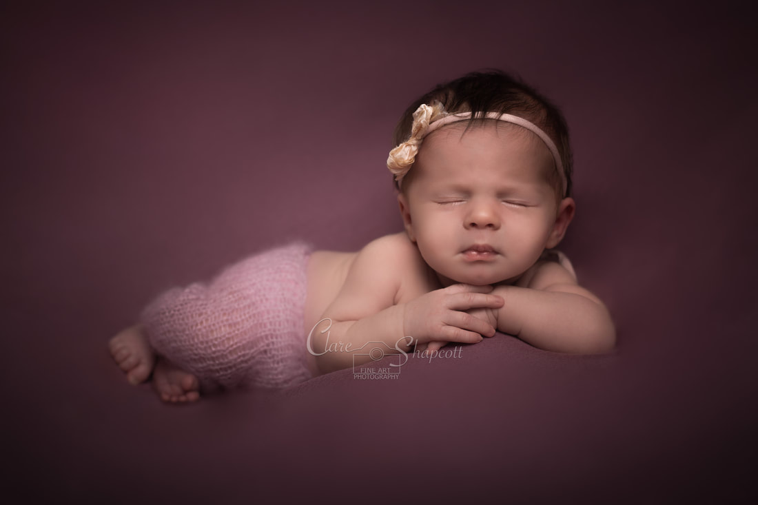 Contemporary photograph of newborn wrapped up with frog theme