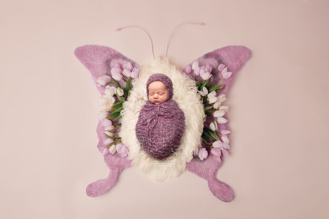 Newborn baby wrapped in purple knitted fabric laying upon pink and white butterfly design with white tulip flowers