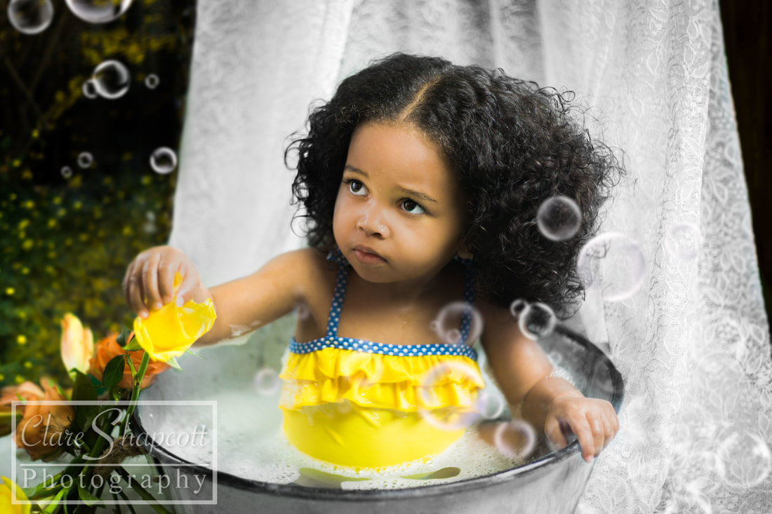 Girl in yellow swimsuit in bath tub with flower