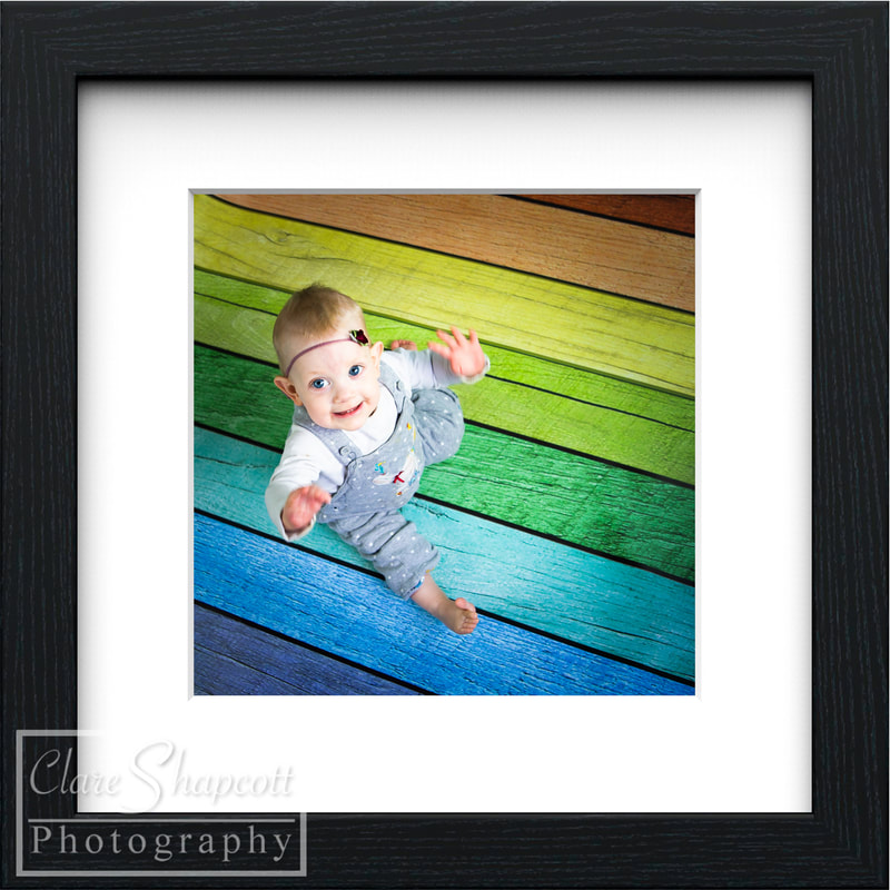 Frame of girl in dungarees on rainbow floorboards