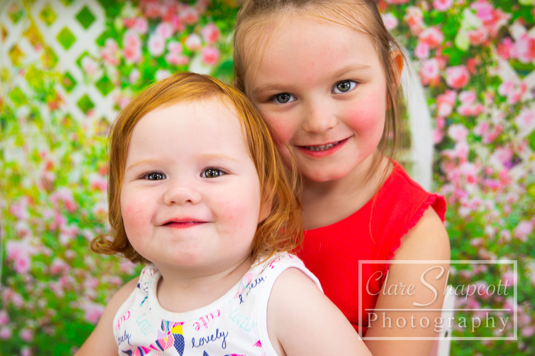 Sibling photograph of sisters on beautiful floral backdrop in Bristol.