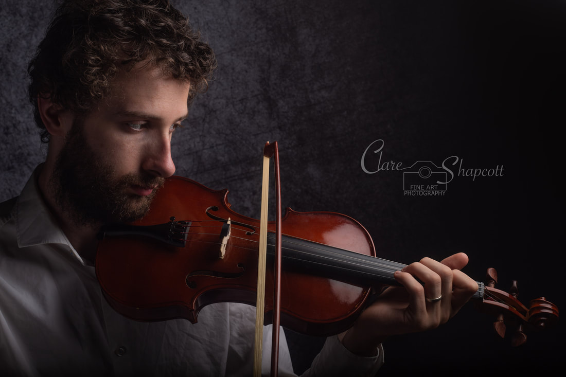 Incredibly dapper bearded man plays violin in front of black background.