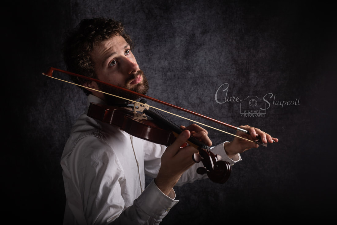 Handsome violinist plays violin whilst looking upwards in Bristol studio.