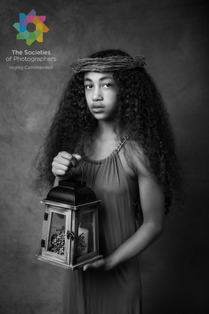 Award winning black and white photograph of girl holding lantern and with fine wooden headpiece.