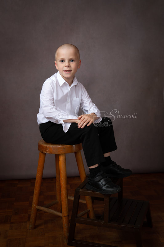 Professional child portrait photograph in white shirt on fancy chair