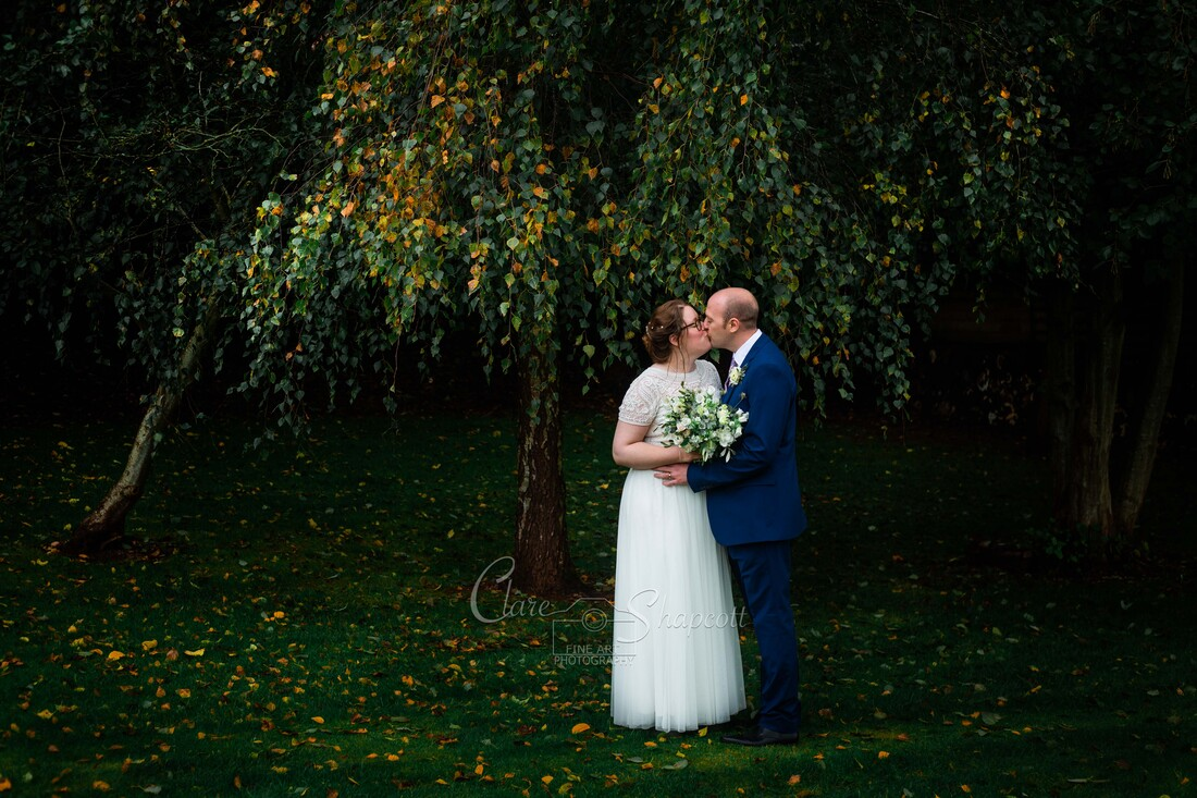 Elegant outdoor photograph of bride and groom kissing next to orange and green tree.