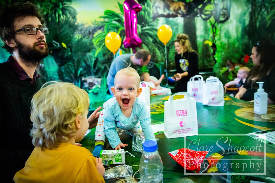Candid photograph of happy girl at birthday party at zoo with balloons