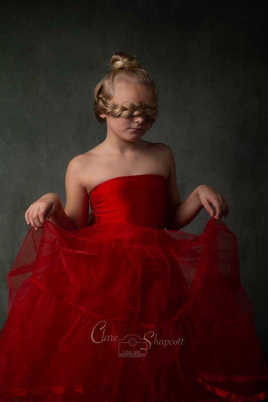 Young girl holds red dress for fine art portrait with her plaited hair forming a blindfold for her own face.