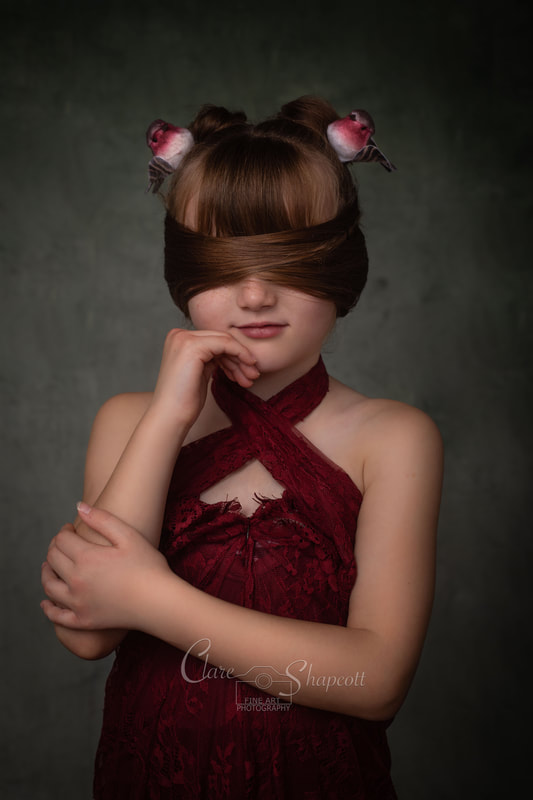 Clare Shapcott photograph of girl in red dress with brown hair arranged to form blindfold over eyes with robin accessories in hair.