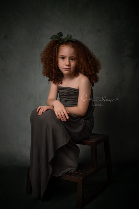 Award winning Photograph by Clare Shapcott photography depicting a young girl with very curly hair sitting on a step wearing a long green gown.