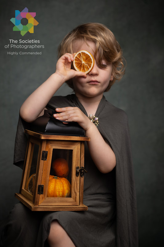 Award winning fine art child portrait of young boy holding orange segment to eye with lantern and pumpkin on his lap