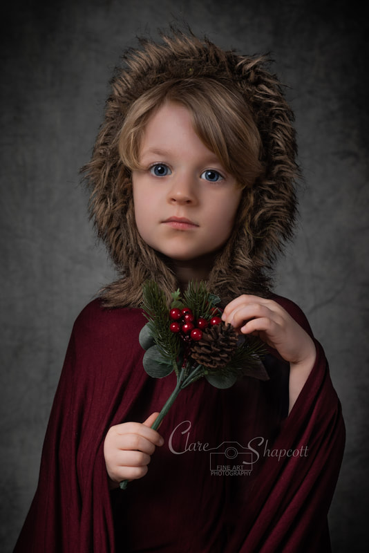 Young boy in red cloak and furry hood elegantly holds christmas holly berry bunch.