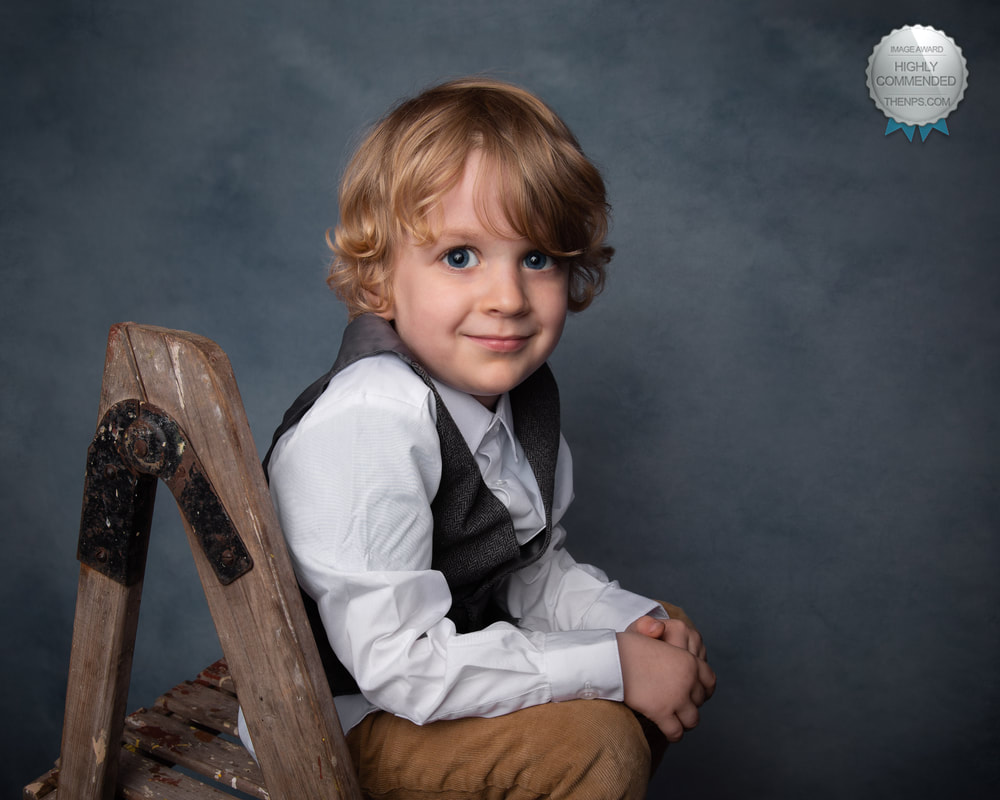 Young boy sits on stepladder in formal attire looking at camera with grey background.
